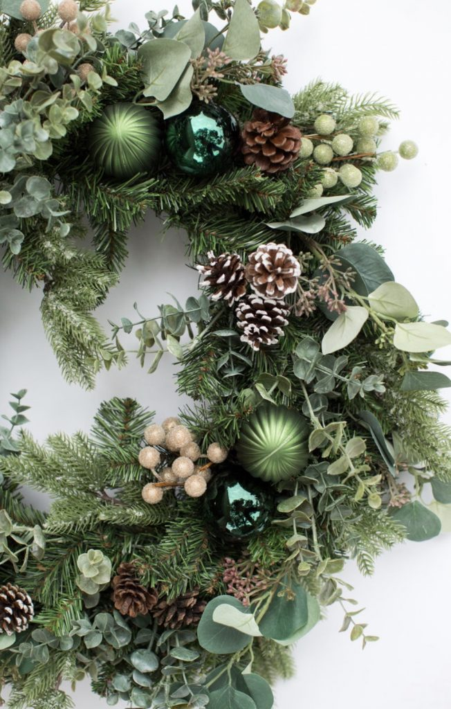 Kristy Mastrandonas Interior Design & Styling - Flower Mound TX - Elegant Winter Woodland Theme Christmas Wreath closeup photo showcasing a mix of seasonal greenery with pine, silver dollar eucalyptus, spiral eucalyptus, pine cones, ball ornaments, creamy gold and green glitter ball stems. The neutral color palette of various shades of green, chocolate brown, and gold will mix with any home decor style.