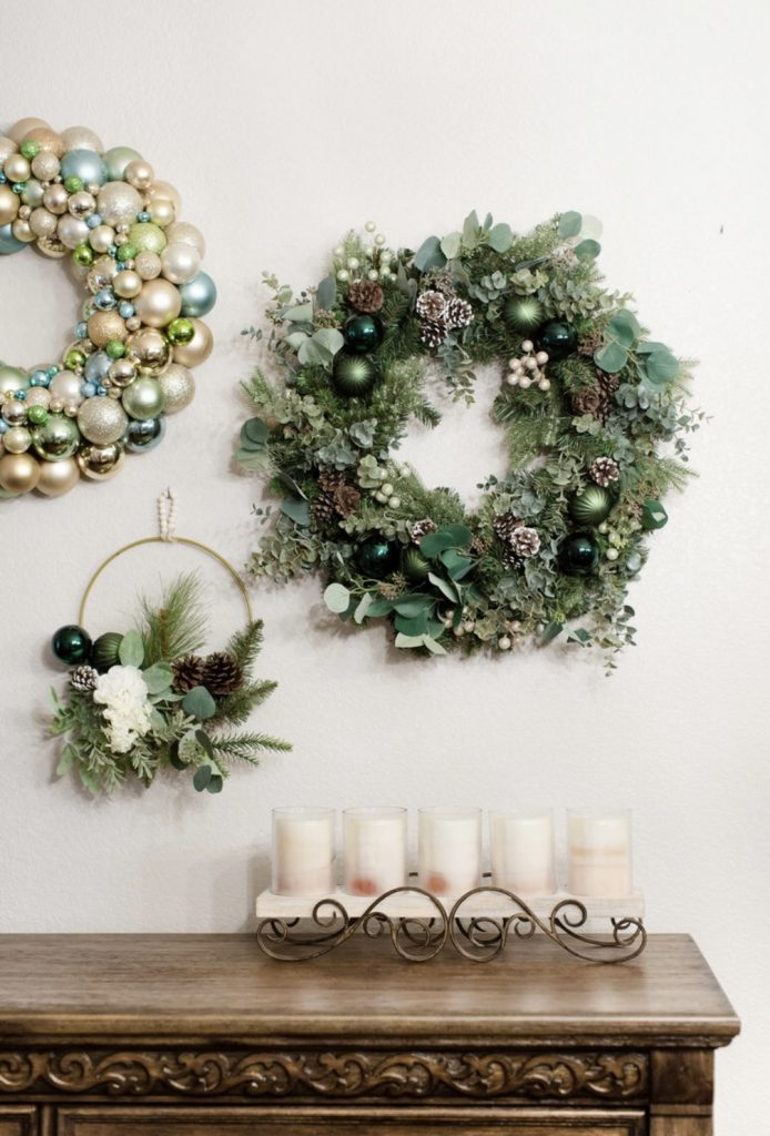 Kristy Mastrandonas Interior Design & Styling - Flower Mound TX - Elegant Winter Woodland Theme Christmas Wreaths showcasing a traditional pine wreath with a mix of seasonal greenery with pine, silver dollar eucalyptus, spiral eucalyptus, pine cones, ball ornaments, creamy gold and green glitter ball stems; a classic Christmas ball ornament; and a Boho-inspired Christmas wreath with a mix of seasonal greenery and ball ornaments on a gold hoop wreath. The neutral color palette of various shades of green, chocolate brown, and gold will mix with any home decor style.